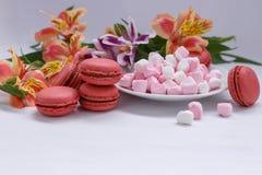 Alstroemeria de macarons, de guimauves et de fleurs sur une table blanche Photos libres de droits