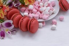 Alstroemeria dei maccheroni, delle caramelle gommosa e molle e dei fiori su una tavola bianca Fotografie Stock