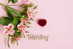 Alstroemeria e contenitore di fiori con l'anello su fondo rosa Immagine tonificata, effetto del film Fotografia Stock