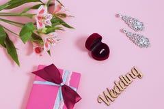 Alstroemeria, pendientes y anillo en una caja en fondo rosado Imagen entonada, efecto de la película Imagenes de archivo