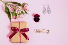 Alstroemeria, pendientes y anillo en una caja en fondo rosado Imagen entonada, efecto de la película Imagen de archivo libre de regalías