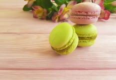 Alstroemeria su un dolce di legno rosa di progettazione, dessert del macaron Immagine Stock Libera da Diritti