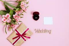 Alstroemeria, tarjeta blanca y anillo en una caja en fondo rosado Imagen entonada, efecto de la película Fotografía de archivo