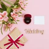 Alstroemeria, tarjeta blanca y anillo en una caja en fondo rosado Imagen entonada, efecto de la película Fotos de archivo