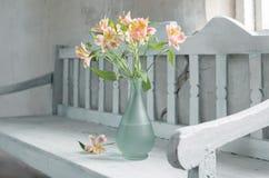 Alstroemeria in vase on old wooden bench Stock Photos