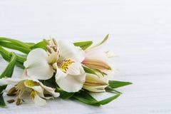 Alstromeria fiorisce nella scatola di legno, accesa candela Immagine Stock