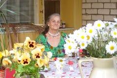 Alt-gealterte Frau, Terrasse, Landhaus, Kamille stockfotografie