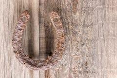 Alt, rostiges Hufeisen der Antike, geregelt auf Nägeln auf einer alten Holzoberfläche Lizenzfreies Stockfoto