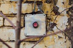 Alt, roter Knopf der Weinlese auf der Backsteinmauer Lizenzfreie Stockfotos
