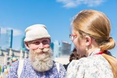 Alt und jung Ein lächelnder älterer Mann mit einem grauen Bart in einem nationalen Kostüm steht mit junger Frau lizenzfreie stockbilder