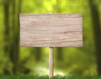 Alt verwitterte das hölzerne Schild, das vom hellen Holz mit Pfosten- und Waldhintergrund gemacht wurde stockbilder