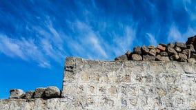 Alt von der Blocksteinwand gegen blauen Himmel Lizenzfreie Stockfotografie