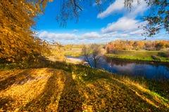 Alta banca del fiume con gli alberi, le foglie sulla terra ed i pescatori nelle barche sul fiume Fotografia Stock Libera da Diritti