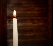 Alta candela bruciante bianca su un fondo di legno vago Fotografia Stock