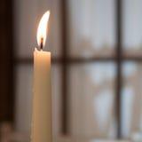 Alta candela bruciante bianca sui precedenti della finestra Fotografia Stock