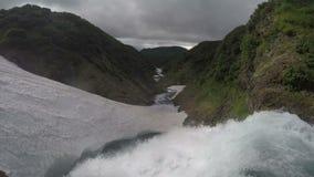Alta cascada de la cascada que cae en campo de nieve almacen de metraje de vídeo