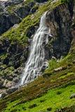 Alta cascata e collina verde nelle montagne Fotografie Stock Libere da Diritti