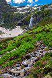 Alta cascata e collina verde nelle montagne Immagine Stock Libera da Diritti