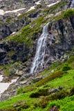 Alta cascata e collina verde nelle montagne Immagine Stock