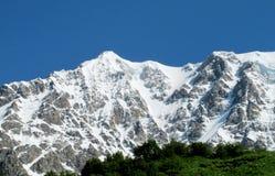 Alta catena montuosa della neve sopra la valle verde Immagini Stock