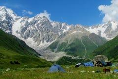 Alta catena montuosa della neve sopra le tende di campeggio in valle verde Fotografia Stock