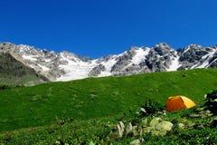 Alta catena montuosa della neve sopra una piccola tenda arancio in valle verde Fotografia Stock