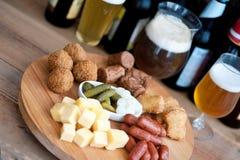 Alta cerveza una variedad de aperitivos para el día de fiesta Imagen de archivo libre de regalías