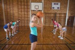 Alta colegiala alrededor para tomar un tiro de pena mientras que juega a baloncesto en la corte Foto de archivo
