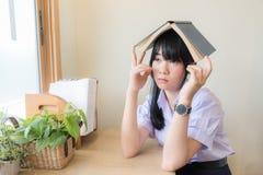Alta colegiala asiática en el iniform que mira hacia fuera la ventana con el libro en su cabeza Fotografía de archivo
