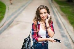 Alta colegiala caucásica joven hermosa feliz con el teléfono elegante verde al aire libre en soleado Imagenes de archivo
