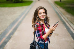 Alta colegiala caucásica joven hermosa feliz con el teléfono elegante verde al aire libre en soleado Imagen de archivo