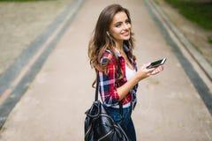 Alta colegiala caucásica joven hermosa feliz con el teléfono elegante verde al aire libre en soleado Foto de archivo libre de regalías