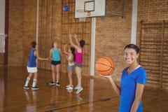 Alta colegiala que lleva a cabo un baloncesto mientras que equipo que juega en fondo Fotografía de archivo