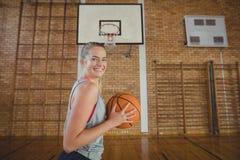 Alta colegiala que se coloca con baloncesto en la corte Imagen de archivo