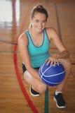 Alta colegiala sonriente que se arrodilla con baloncesto en la corte Imágenes de archivo libres de regalías