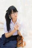 Alta colegiala tailandesa en el uniforme y los vidrios que se sientan con la guitarra Fotografía de archivo libre de regalías