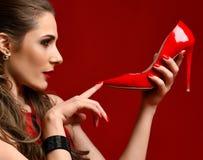 Alta collina della bella della donna scarpa rossa castana della tenuta su rosso scuro Fotografie Stock