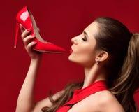Alta collina della bella della donna scarpa rossa castana della tenuta su rosso scuro Fotografia Stock
