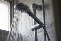 Alta corrente dello spruzzo d'acqua di pressione che versa da una testa di doccia tenuta in mano Immagine Stock