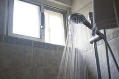 Alta corrente dello spruzzo d'acqua di pressione che versa da una testa di doccia tenuta in mano Immagine Stock Libera da Diritti