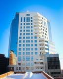 Alta costruzione con le grandi finestre di vetro sui precedenti del cielo Fotografia Stock