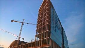 Alta costruzione in costruzione con le gru a torre nella sera Immagine Stock