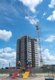 Alta costruzione in costruzione con la gru ed il campo da giuoco Fotografia Stock Libera da Diritti