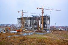 Alta costruzione in costruzione con le gru e molte automobili Fotografia Stock