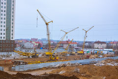Alta costruzione in costruzione con le gru e molte automobili Immagine Stock