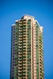 Alta costruzione del condominio di aumento contro il fondo del cielo blu Fotografia Stock