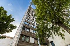 Alta costruzione di appartamento a più piani con gli alberi contro cielo blu Immagini Stock Libere da Diritti