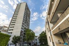 Alta costruzione di appartamento a più piani con gli alberi contro cielo blu Fotografie Stock Libere da Diritti