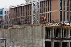 Alta costruzione di aumento che va in su gli installatori stanno lavorando alla costruzione dell'edificio Fotografia Stock