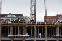 Alta costruzione di aumento che va in su gli installatori stanno lavorando alla costruzione dell'edificio Fotografia Stock Libera da Diritti